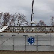 Auf der Rückseite des Hallendaches werden die verpackten Eternitplatten auf den LKW gehoben, vorne wird neu gedeckt